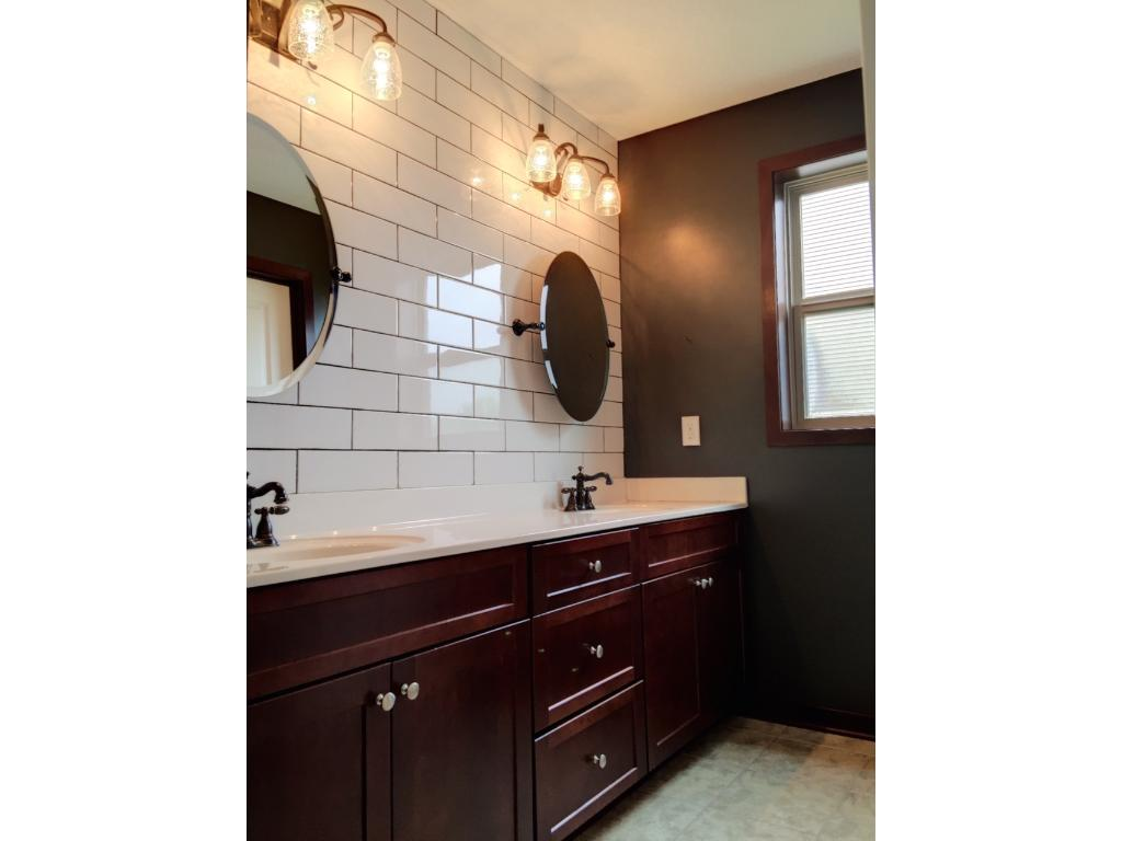 Updated bath with new tile, lighting, and mirrors. Dual sink vanity with lots of storage connected to private bath/shower space to allow more than one person the room to get ready.