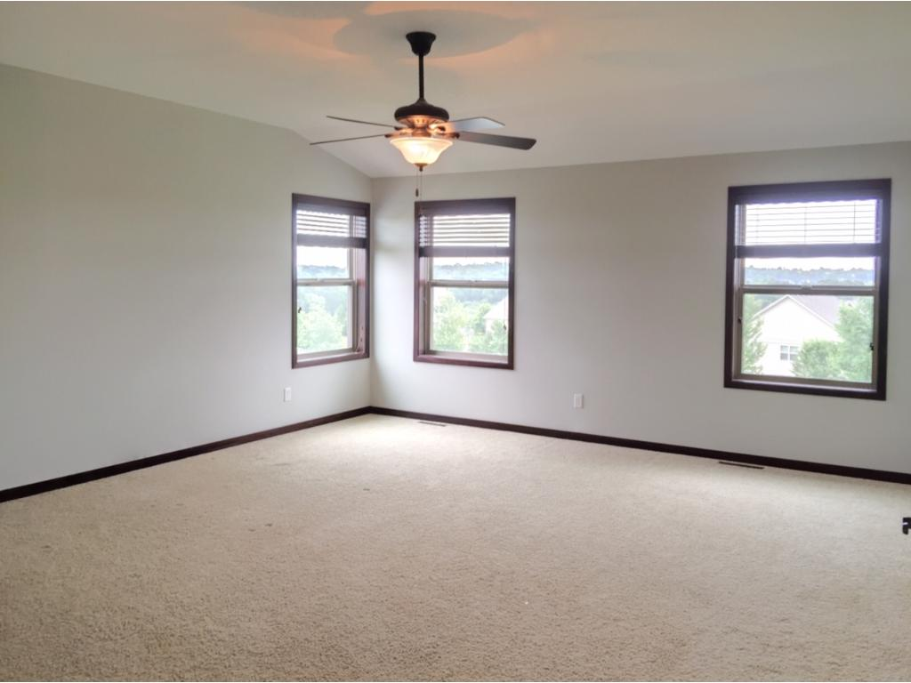 Spacious master with wood blinds and ceiling fan and dual walk-in closets.