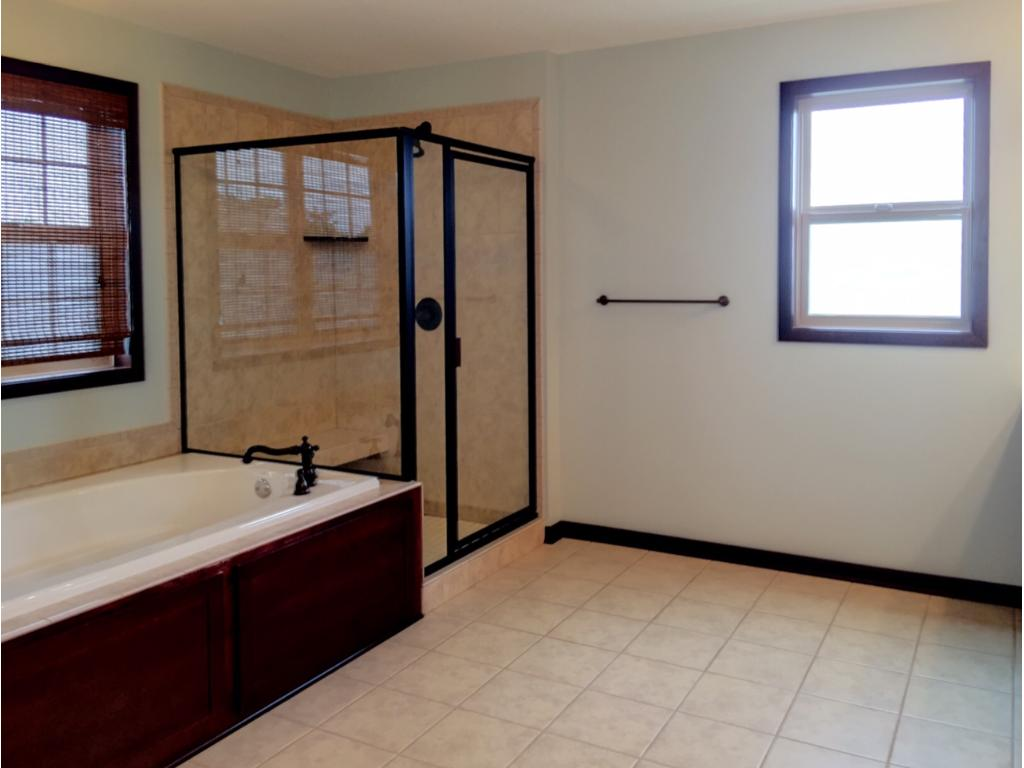 Oversized jetted tub and spacious walk-in shower complete with built-in bench.
