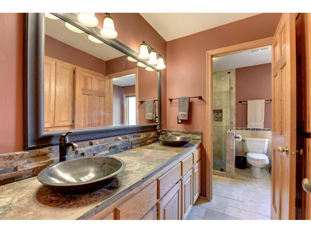 Spa like bathroom is fully updated featuring whirlpool tub, separate walk in glass shower, dual vanity, and plenty of cabinet space.
