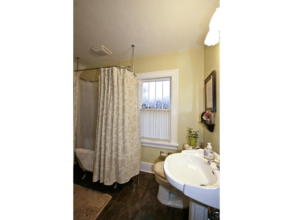 Full bathroom on upper level, with claw foot tub and slate flooring.