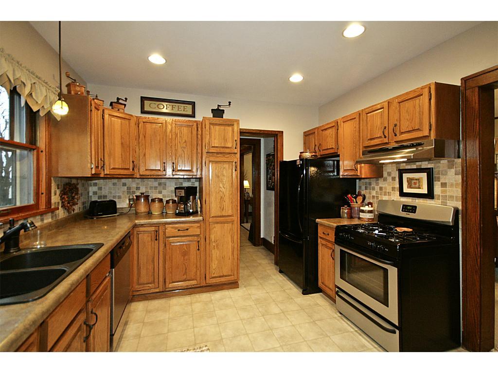 Oak cabinets, recessed lighting, newer appliances, newer kitchen sink, counters and tile backsplash.