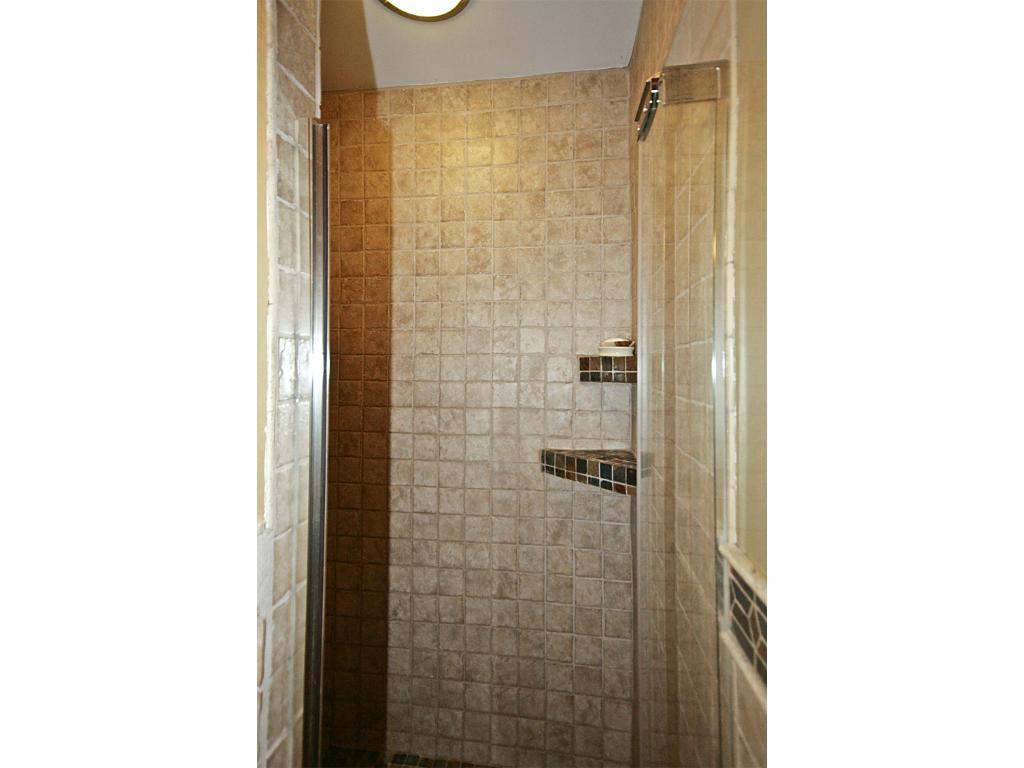 Tile shower with glass door.