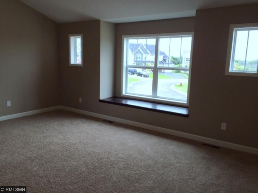 HUGE vaulted master bedroom with bench seat and multiple windows.