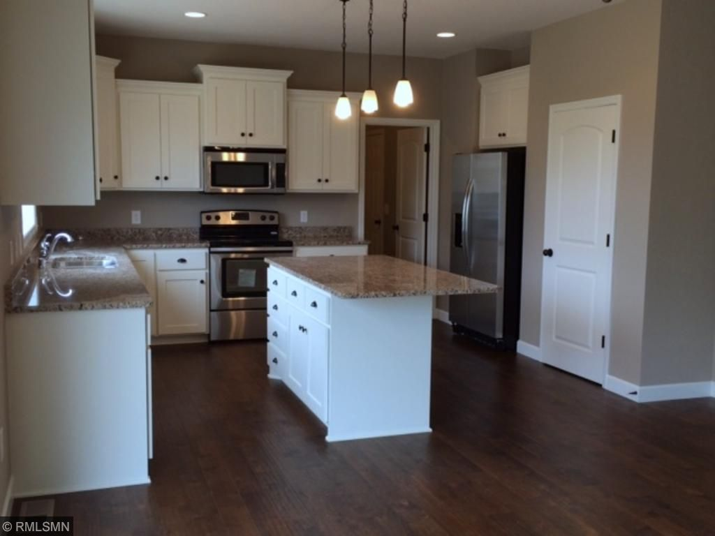 Another angle of the open kitchen. White enameled cabinets/island, stainless steel appliances, granite counters, wood floors.