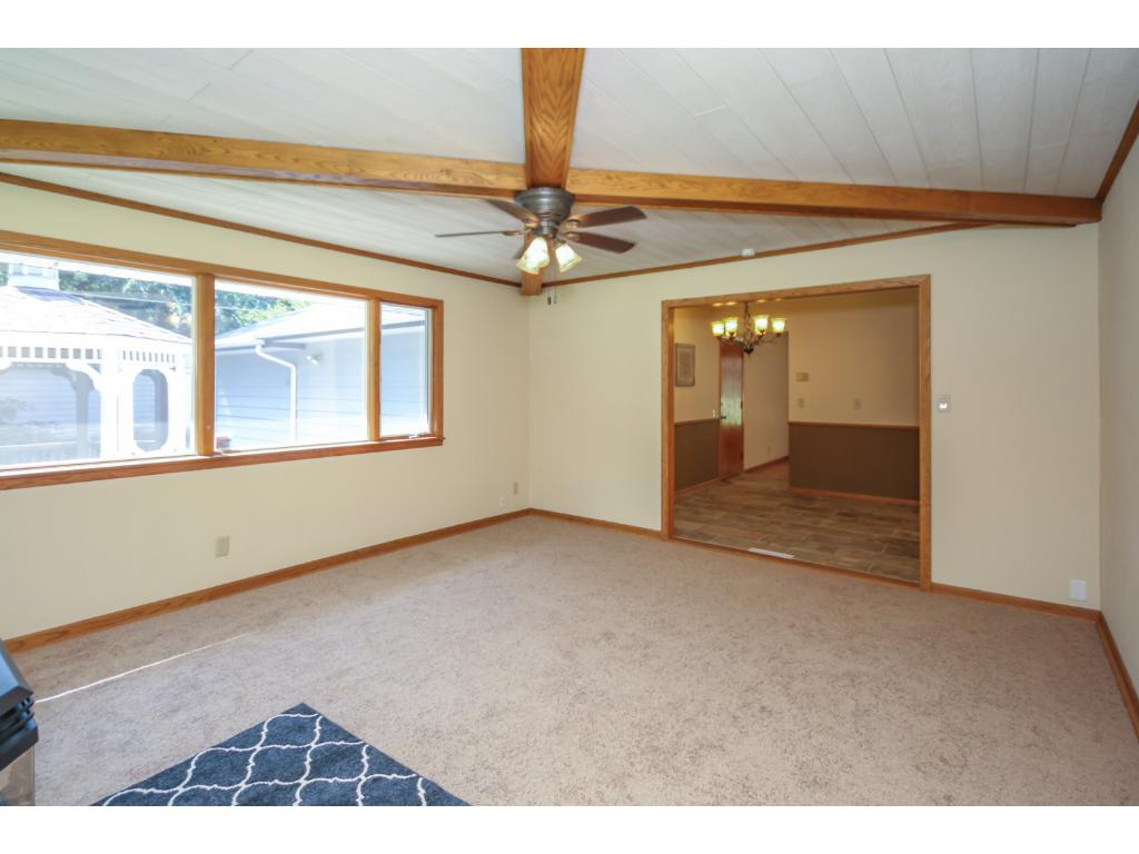 New carpet, paint and beamed ceilings complete the look of this oversized, sunny room.