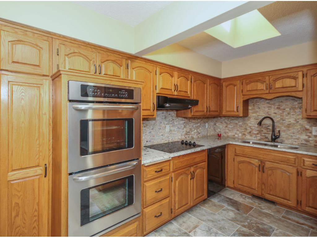 This kitchen is FILLED with cabinet space and has top of the line new granite countertops, new stainless steel double oven, cooktop and side by side refrigerator