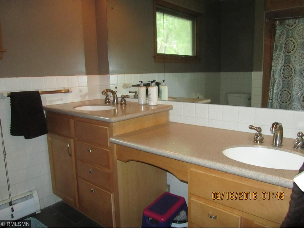 Main floor bathroom, tile floor, double sink, hard surface countertop