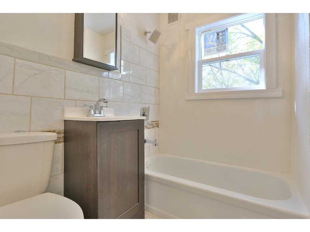 Full bathroom with new ceramic tile, vanity, toilet, shower, lighting, mirror and in-wall fan.