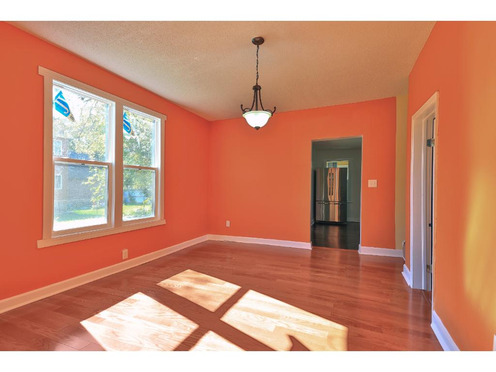 Dining room with brand-new hardwood flooring and ENERGY STAR windows.