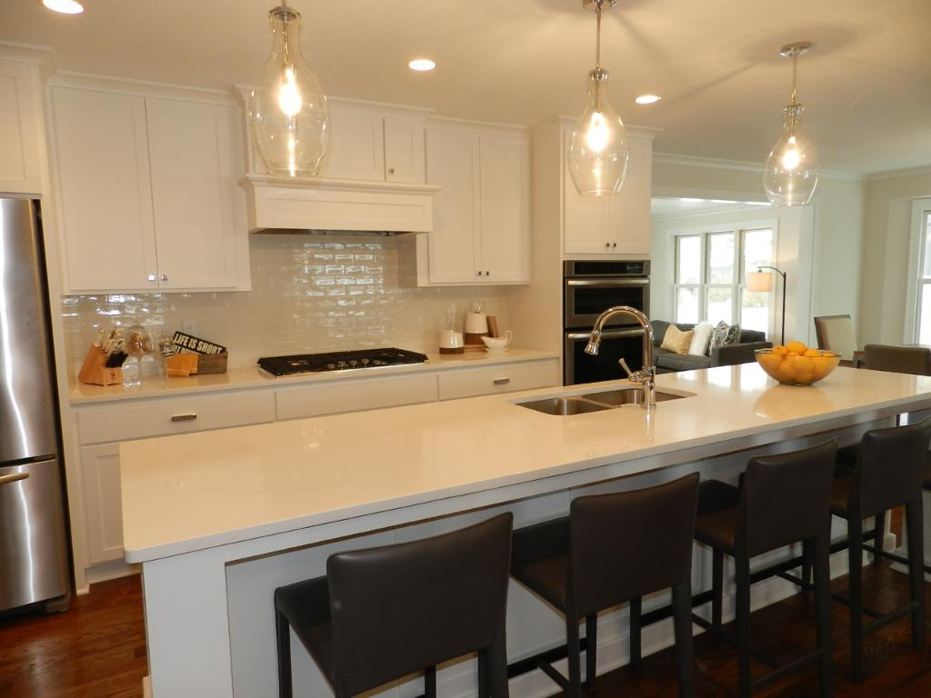 Another view of the 12x15 Kitchen. Soft close custom cabinets, built-in hood, recessed lighting, and 3 glass pendants over the island. Island seating is great for casual dining, and visiting with the cook(s) without being in the Kitchen.