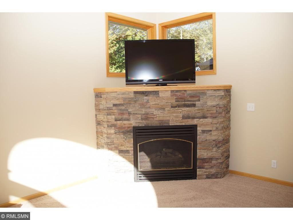 New stone fireplace front and carpet in the vaulted living room.