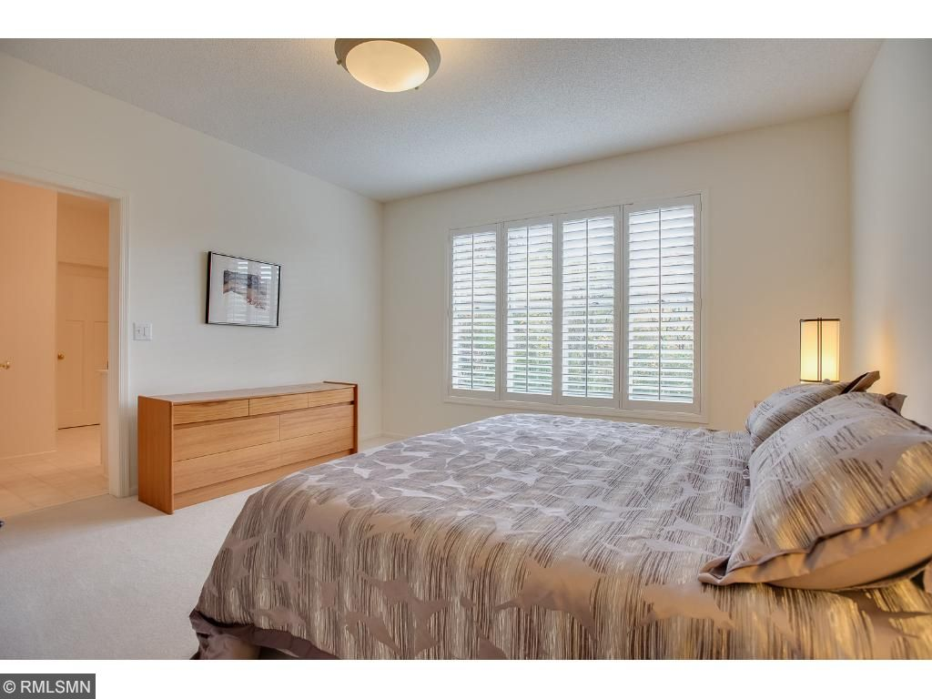 Main level owners suite enjoys south exposed natural light with plantation shutters and full sized ensuite bath.