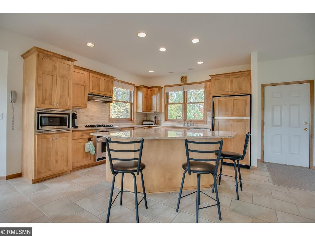 Bright open kitchen has oversized granite island ideal for prepping and entertaining.