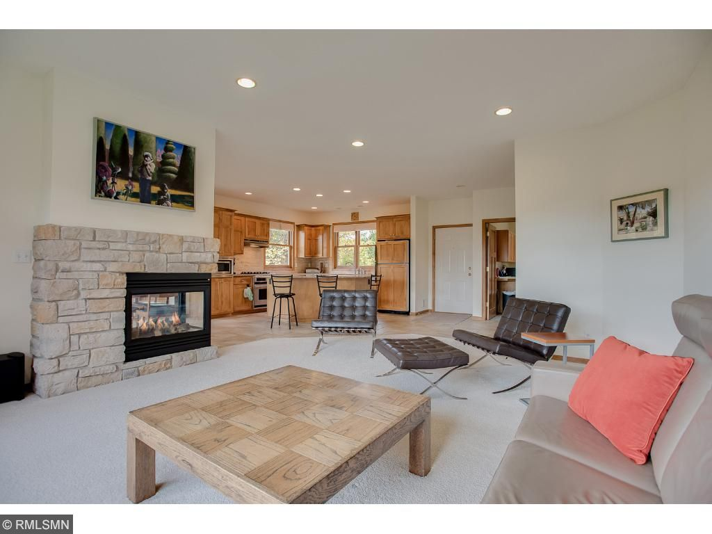 Main level living room is a desired open floorplan including the kitchen and dining areas, which all share the comfort of the 3-way fireplace.