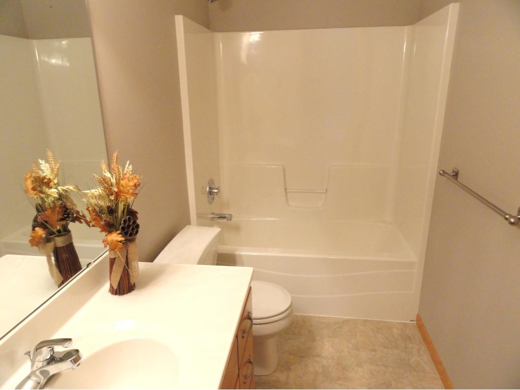 Main level full bathroom has a long vanity and new flooring and paint.