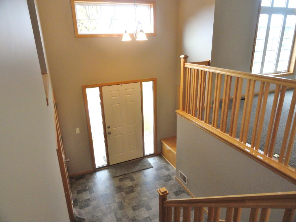 Large entry has new flooring, bright windows, closet, built-in bench with storage and decorative shelf.