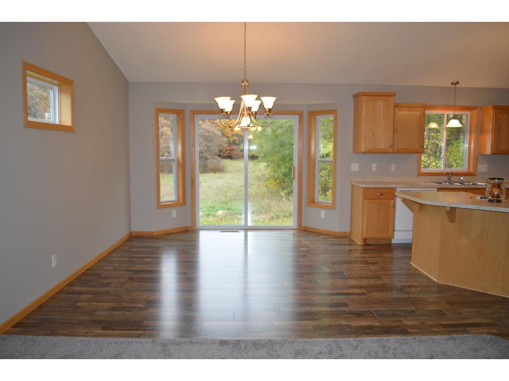 Gorgeous new laminate flooring gleams in this vaulted dining area with bayed window.