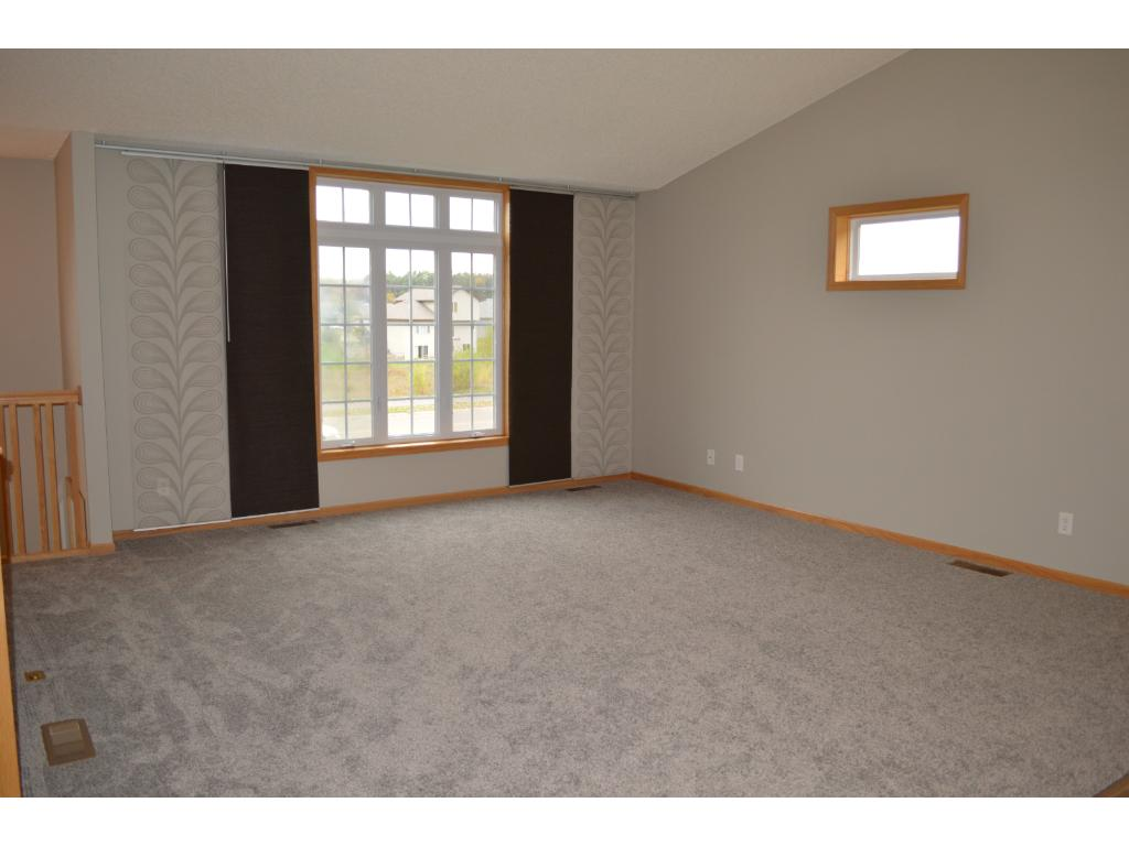 Open floor plan with vaulted living room has Low-E windows, new carpet and extra windows for lots of natural light.  New paint and flooring throughout entire main level.