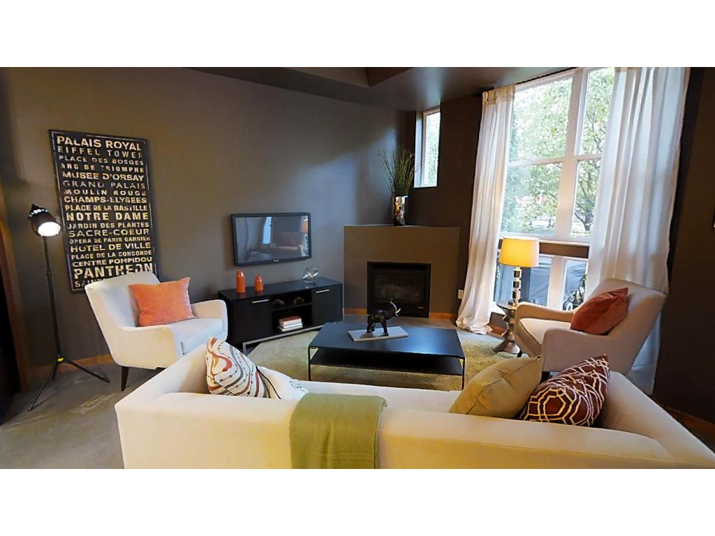 Living room is bathed in natural light and features a gas fireplace