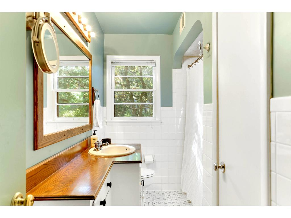 This beautifully Tiled Main Level Full Bath, with window views of the private backyard, is complete with a large linen closet and plenty of vanity storage!