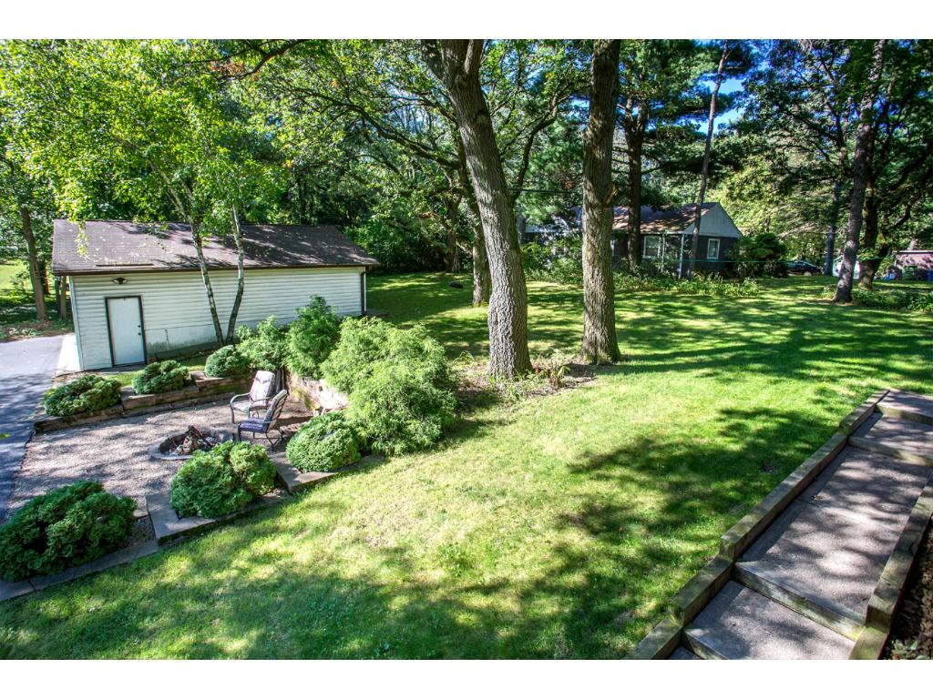 View of the very spacious backyard from Deck! Includes an invisible fence and many varieties of mature trees!