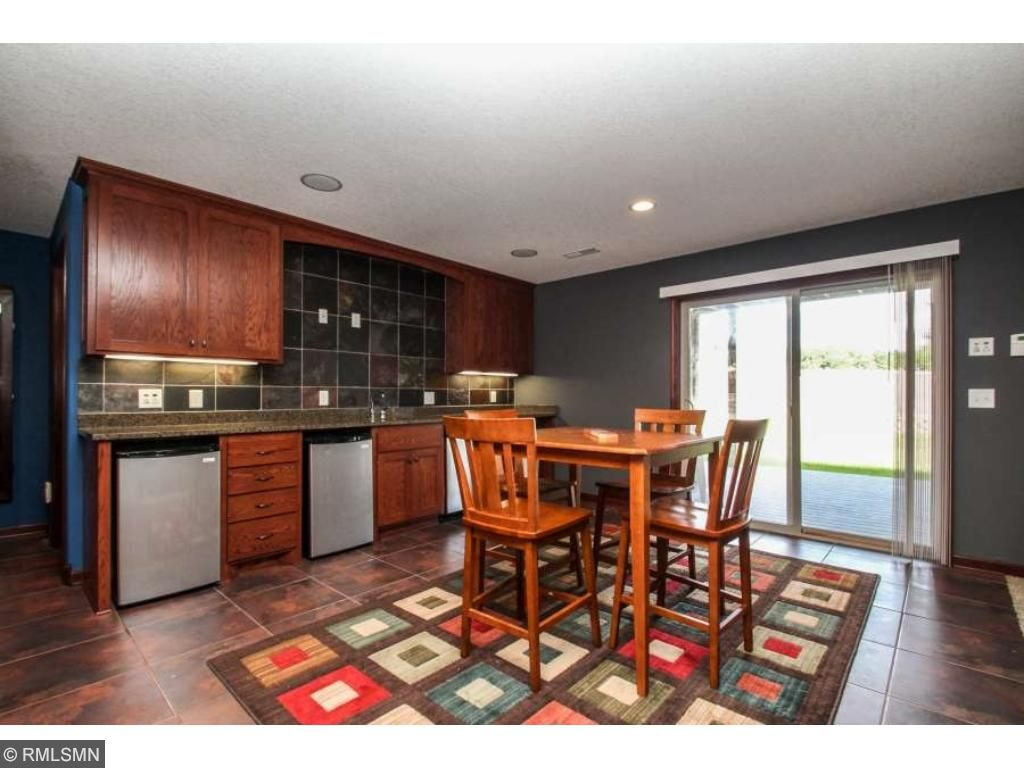The basement is the perfect place for entertaining with full wet bar, mini-fridge, walk-out to lower level maintenance-free deck!
