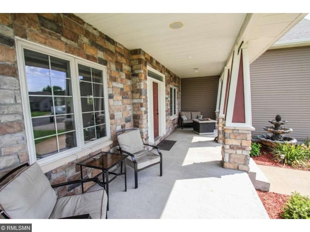 Concrete front porch with stone and pillars greets your guests!