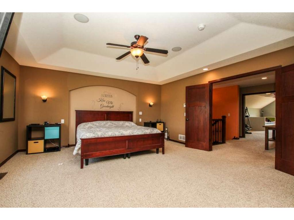 Generous owner's bedroom with soft tray vault, wall inset, ceiling fan, double doors, walk-in closet!