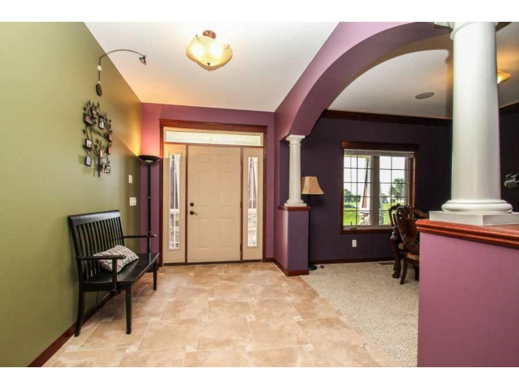 Welcoming foyer with hardwood floors, transom and sidelights surround front door, pillars to dining room!