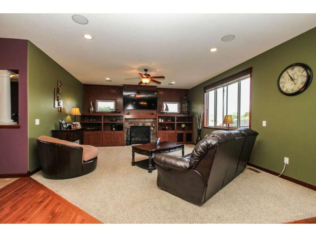 Relax in the great room with built-ins, transom and picture windows, gas fireplace, ceiling fan!