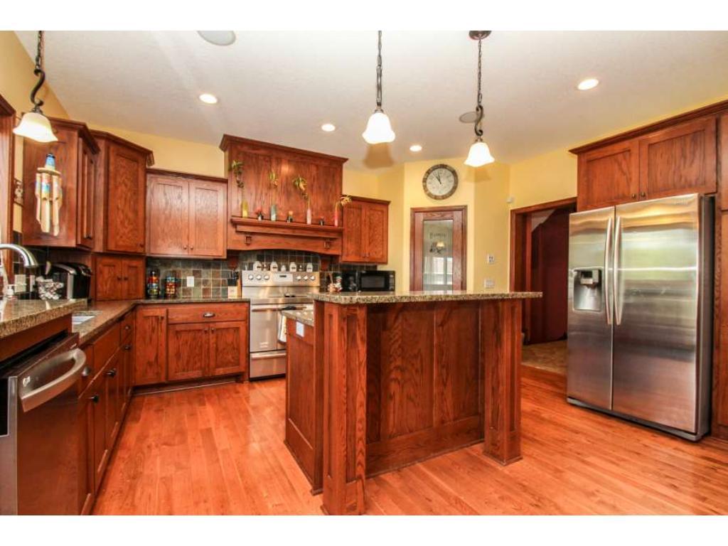 An amazing kitchen with walk-in pantry, granite countertops, center island, industrial range, custom cabinets, pendant lighting!