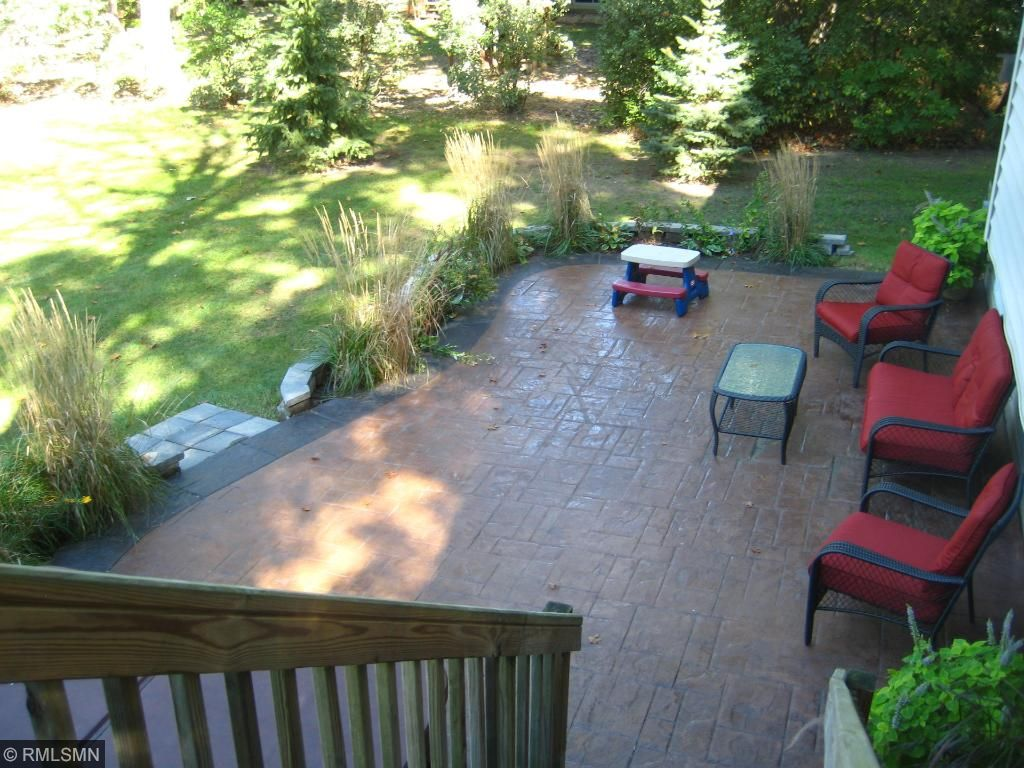 Rear view toward paver block patio and walk-down deck. Large backyard, firepit and privacy fence.