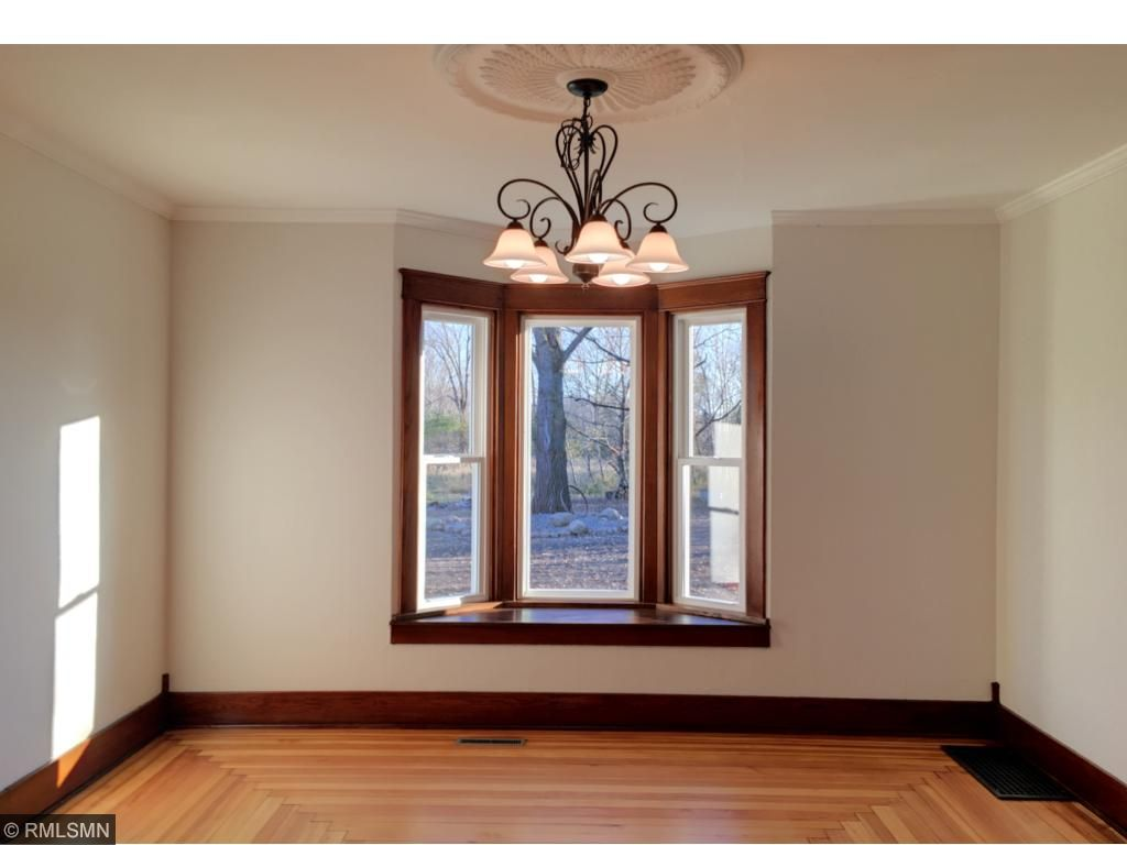 Separate dining room with awesome hardwood floor design, bay window and grand light fixture.