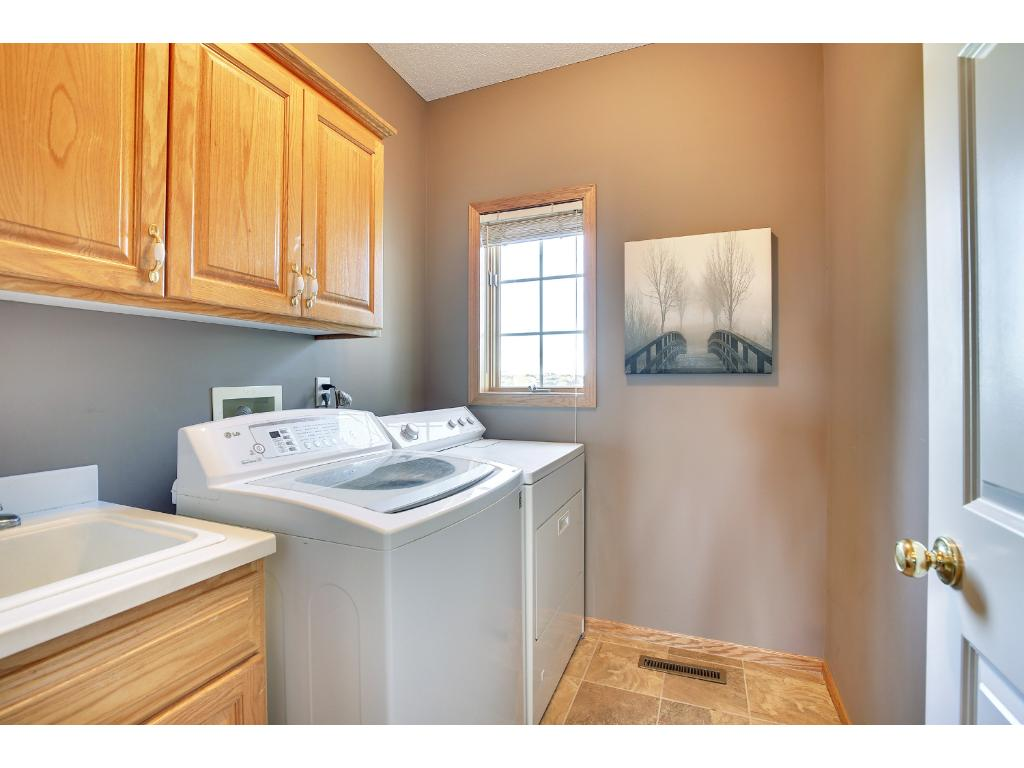 Convenient main floor laundry with sink and storage