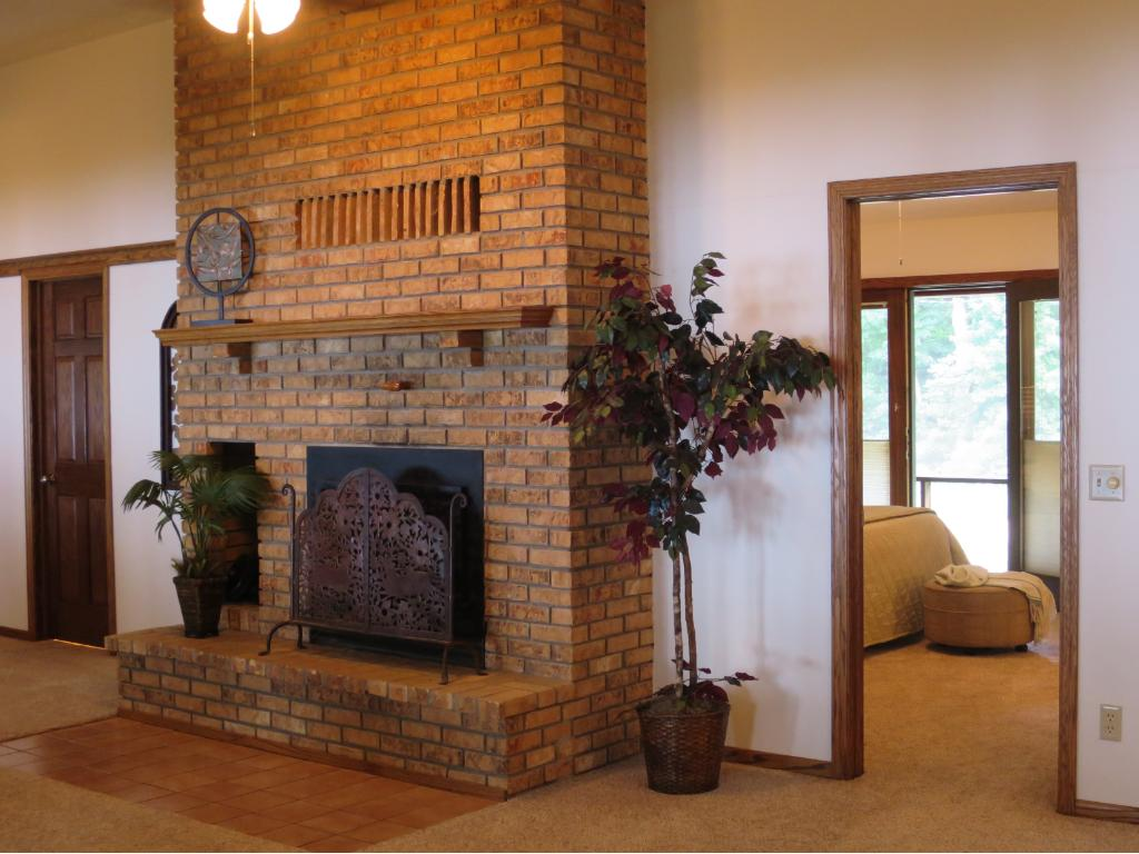THIS IS THE WOOD-BURNING FIREPLACE THAT ANCHORS THE GREATROOM, WITH A GLIMPSE INTO THE MASTER BEDROOM THAT OPENS TO THE SCREEN PORCH.  THE DOOR AT THE LEFT IS THE MAIN FLOOR FULL BATH.