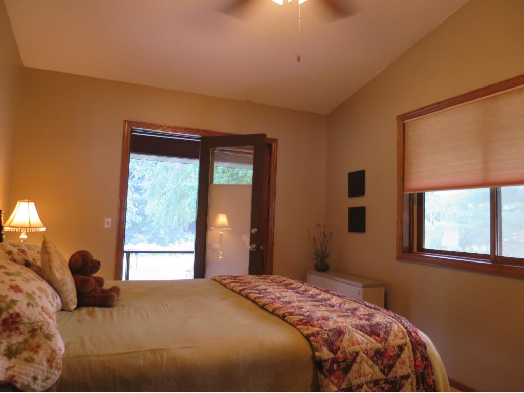 THE 2ND MAIN FLOOR BEDROOM  ENJOYS BREEZES & ACCESS TO THE WRAP-AROUND SCREEN PORCH, AND A WALK-IN CLOSET !