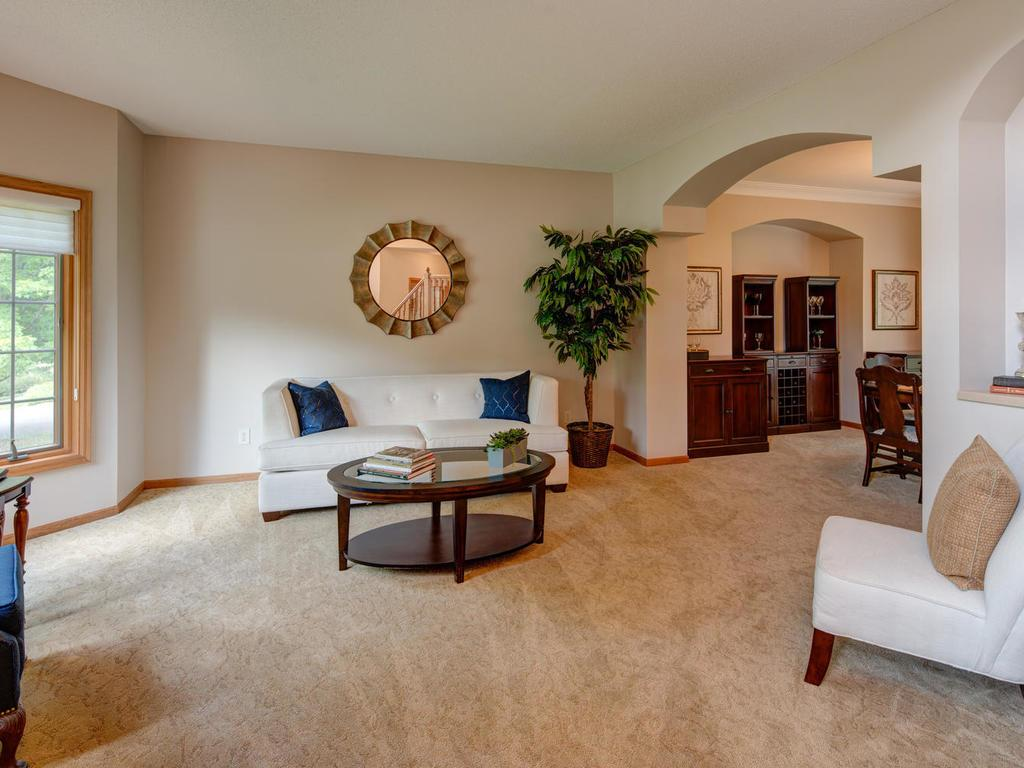 Living rooms flows off foyer area and into tranquil dining room with views of trees and backyard.