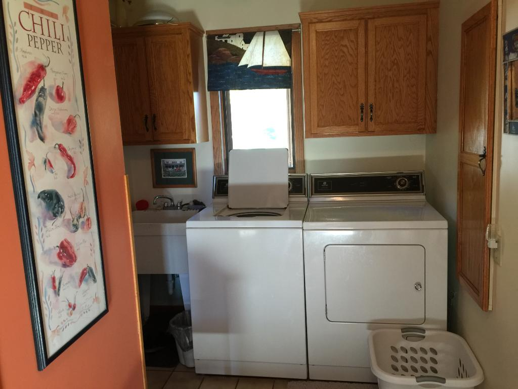 Main floor laundry has cabinets and built in ironing board.