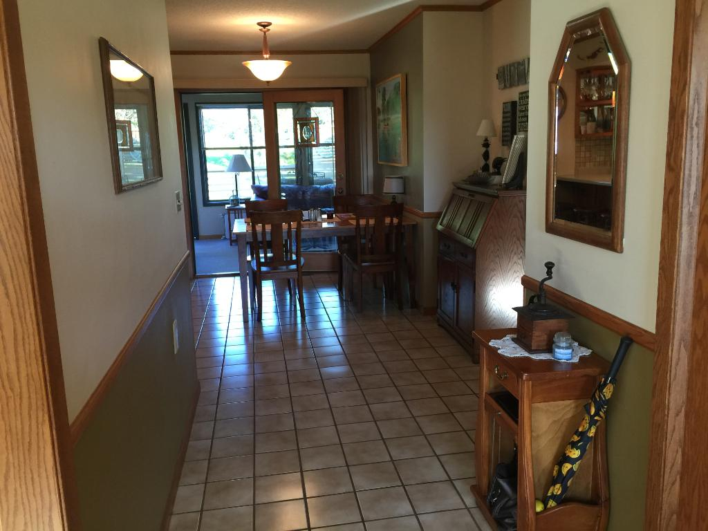 Friendly foyer and front door entrance with ceramic tile floor.