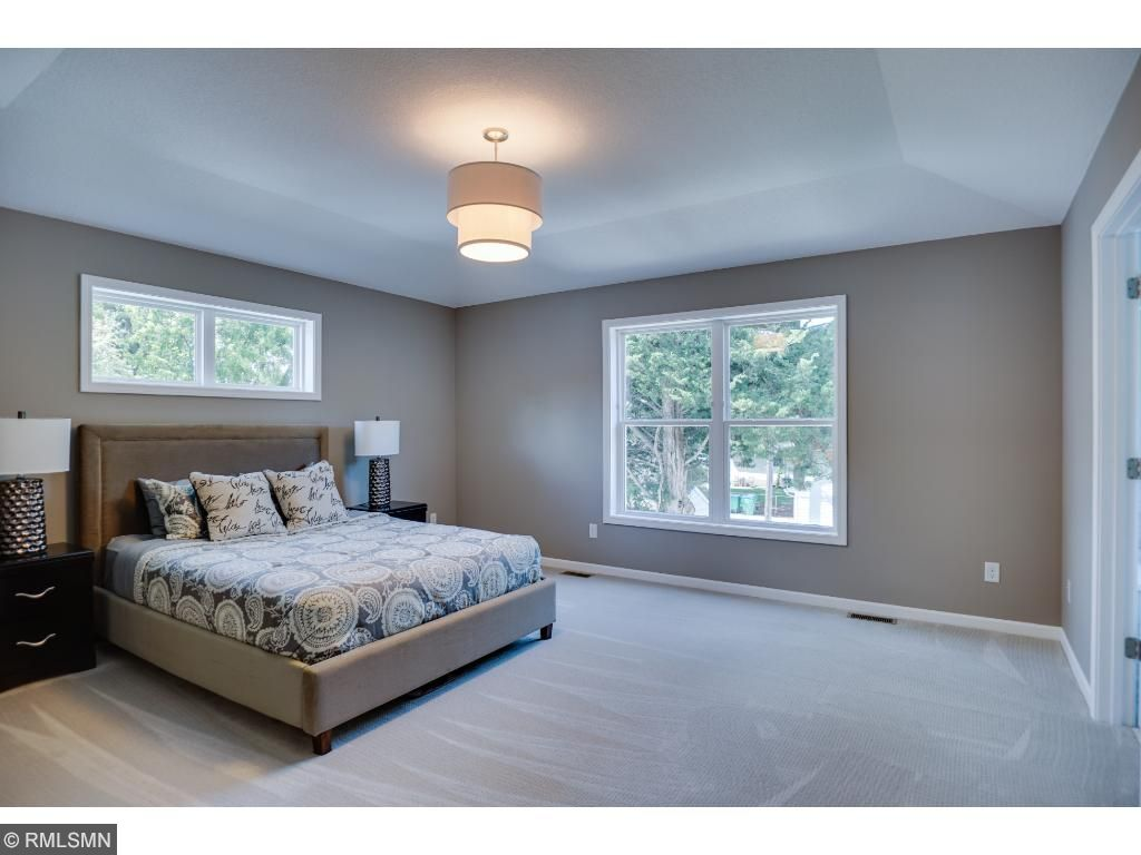 Spacious and well lit master featuring 9' ceilings, along with his+hers master closets, and en suite bath
