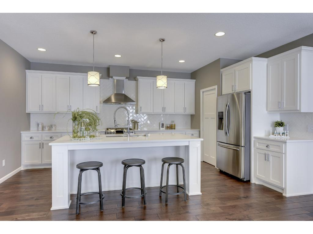 Spacious kitchen with custom cabinets and quartz counters