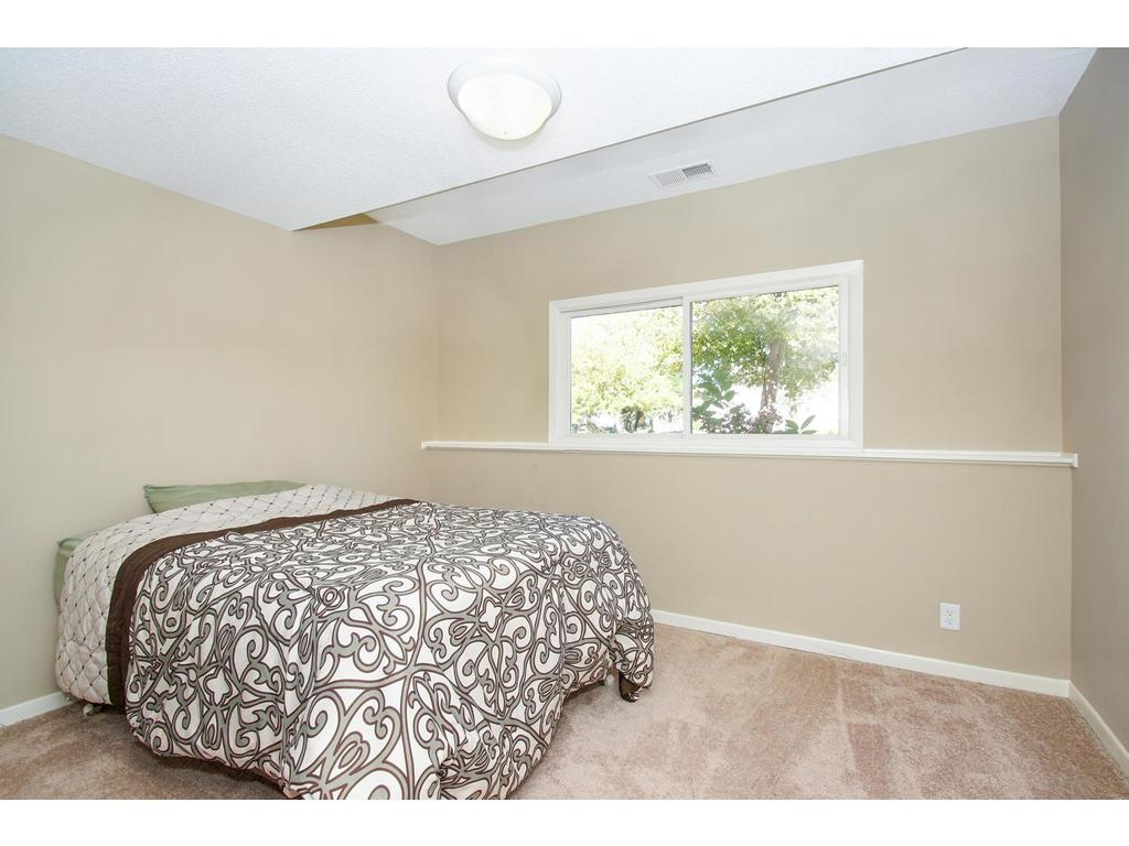 The vaulted ceiling in this lower level bedroom provides an open feel to this space.
