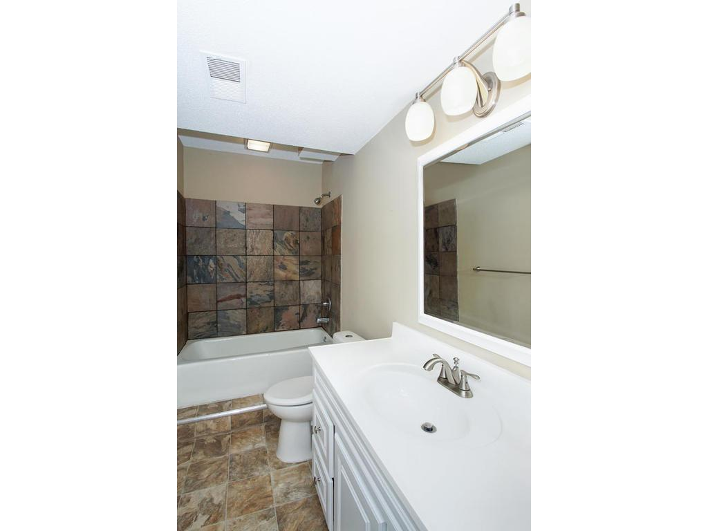 The lower level full bath, complete with custom tile work in the shower/tub.