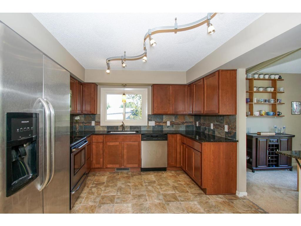 Custom features in the remodeled kitchen include the granite countertops and track lighting.