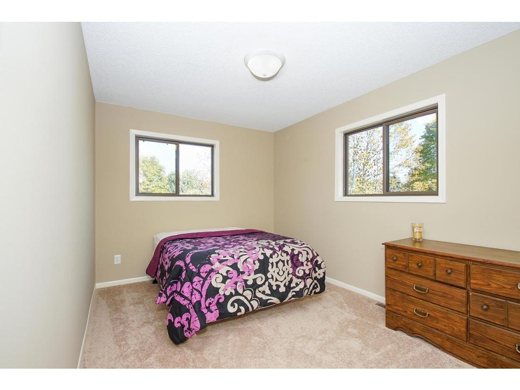 This upper level bedroom is brightened by light exposure on two sides.