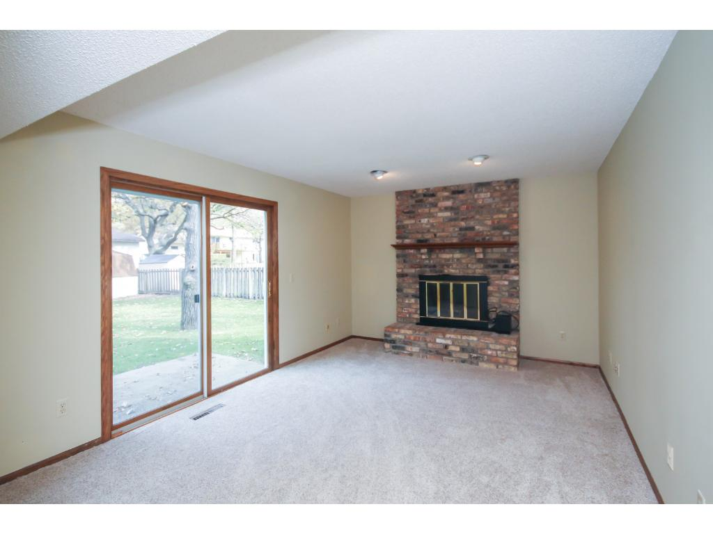 Informal living or den area, perfect for snuggling up to the wood burning fireplace & walkout.