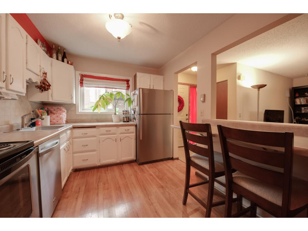 Updated kitchen features new shiny stainless steel appliances, new countertop and brushed nickel lighting above.