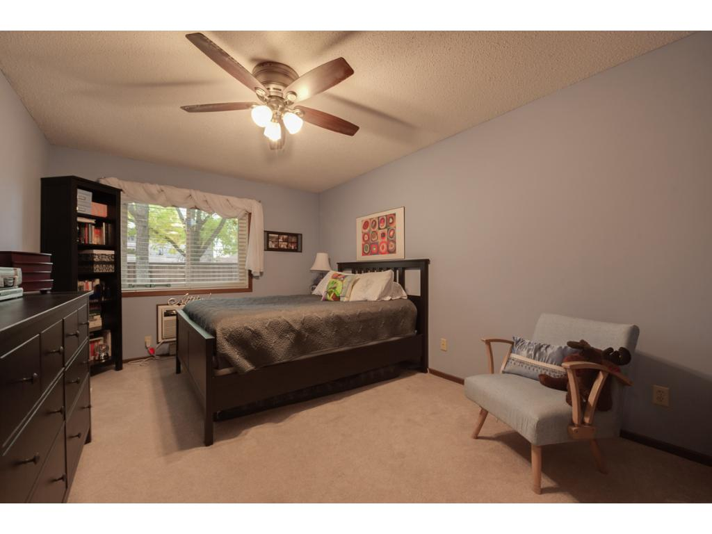 The spacious master bedroom features a large window and lit ceiling fan.