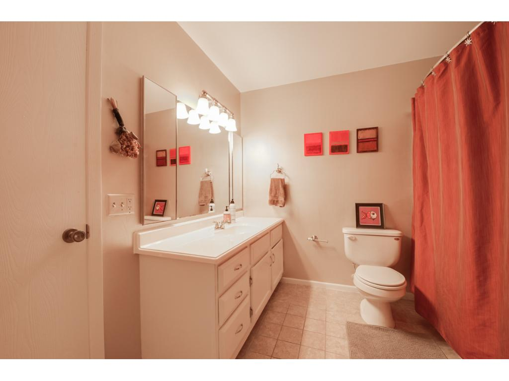 The full bath includes an oversized single storage vanity with new countertop, expansive mirror with built-in medicine cabinets & brushed nickel lighting above.